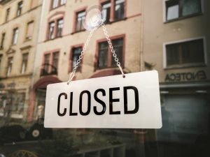 Closed sign inside business door to represent closings due to COVID-19